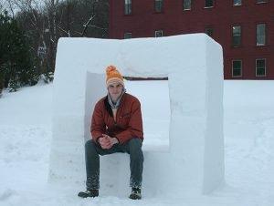 Sculptor Zac Benson sitting on an ice sculpture