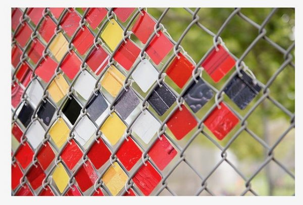 Photographs printed on metal and wired to a chain link fence