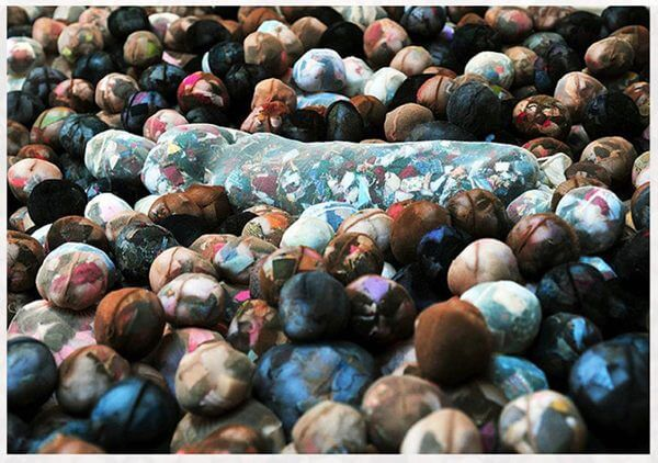 A photograph of a group of fabric figures arranged as if gathering around a casket
