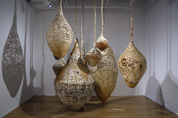 An installation of hanging vessels made from homemade paper