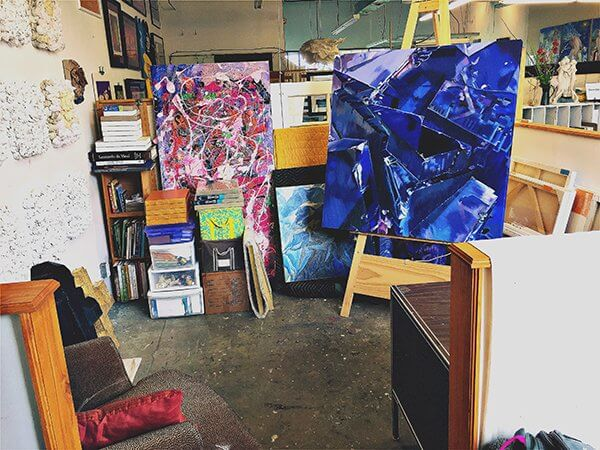 Large close-up paintings of flowers and crystals in an artist's studio