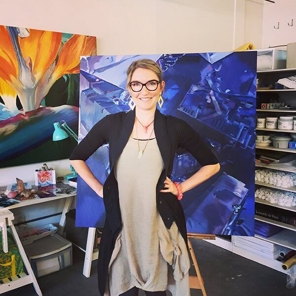 An artist poses in front of her large close-up paintings of flowers