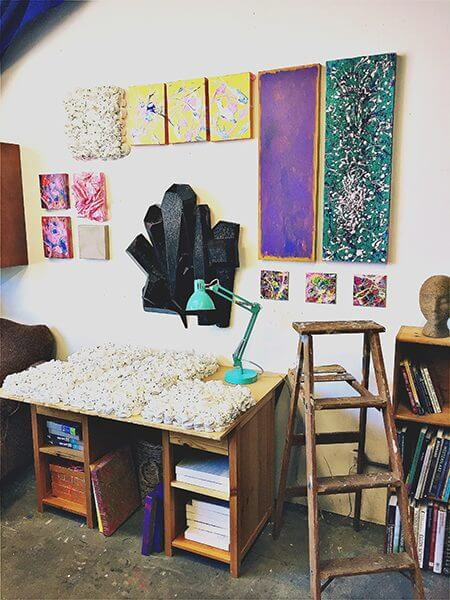 Paintings of crystals and flowers line the wall of an artist's studio