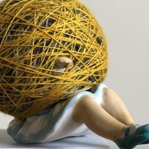 scultpure by of a woman caught in a ball of string