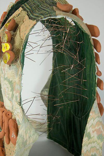 A close-up of an art piece inspired by a guard's vest, with needles lining the inside of the vest