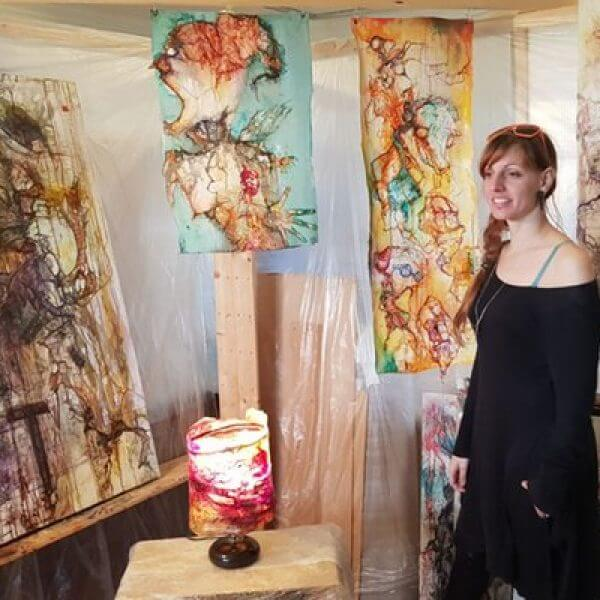 An artist in her studio of abstract mixed media wall hangings