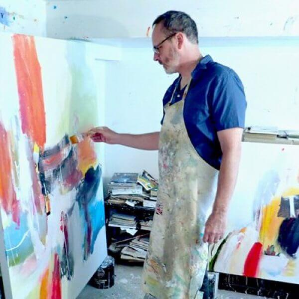 A painter works on a canvas in his studio