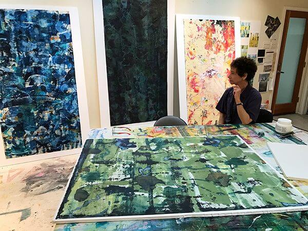 Artist Naomi Schlinke sits in her studio among her abstract paintings