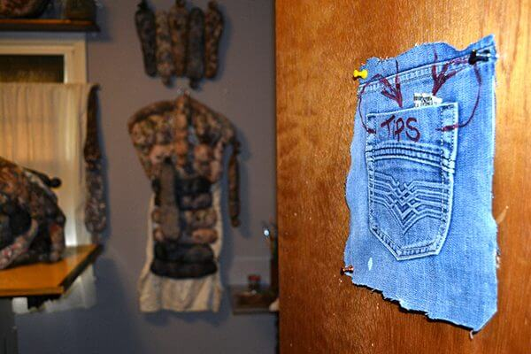 "A cut out back jean pocket with the word ""tips"" written on it, pinned to a door"