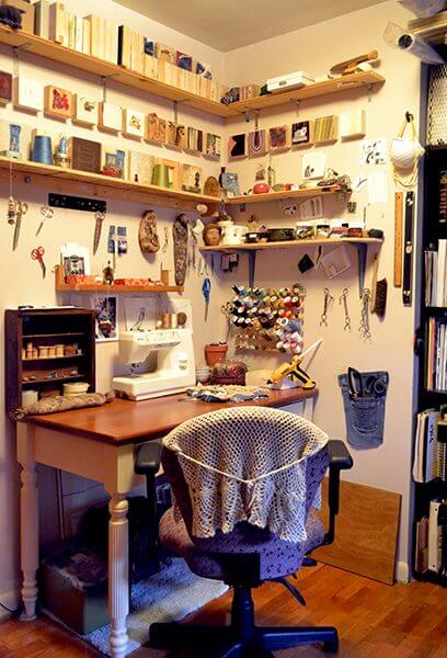 A fiber artist's studio desk with spools of thread and a sewing machine