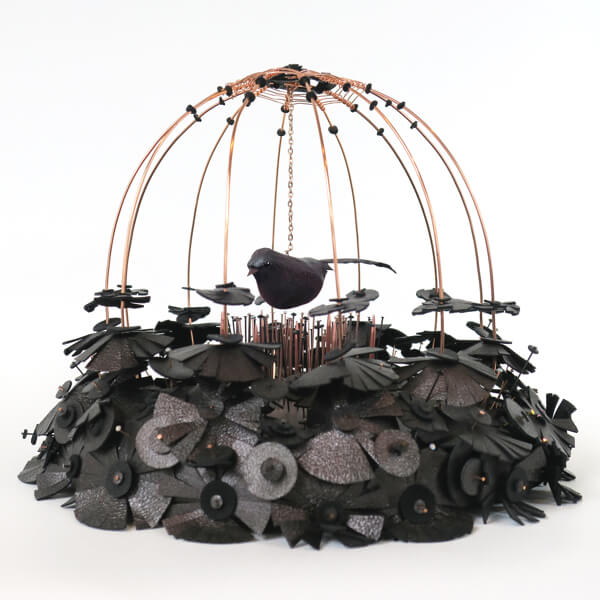 Photo of an artifical bird in a cage made of knitting needles and leather