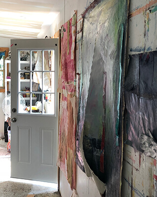 Hanging paintings on canvas in an artist's studio