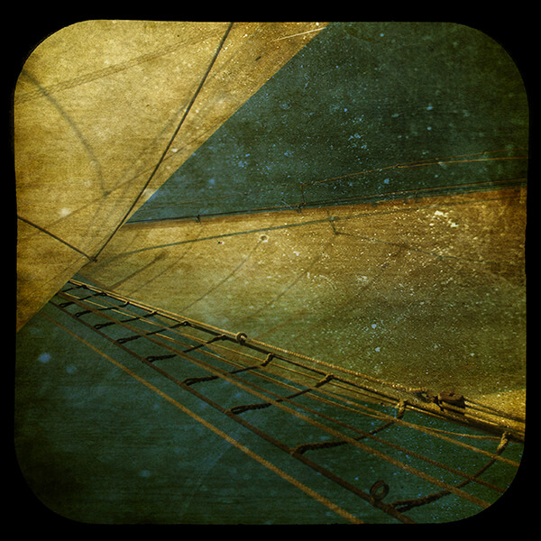 Edited photograph of the mast of a sailboat among a dark background