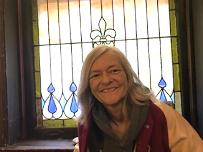 Headshot of poet Pamela Sumners with a stained glass window in the background