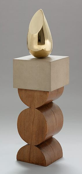 A golden sculpture on a pedestal of limestone and wood