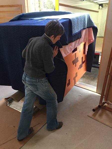 An artist moves her pieces on a rolling crate  into a new studio