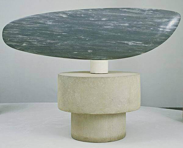 A wide blue-gray marble sculpture on a pedestal of white marble and limestone