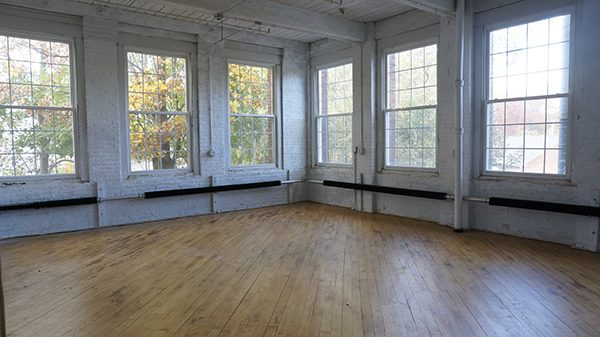 An empty artist's warehouse studio, with wood floors and high-ceiling windows