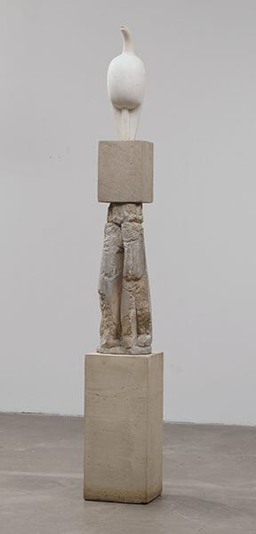 A white marble sculpture on a three-part limestone pedestal