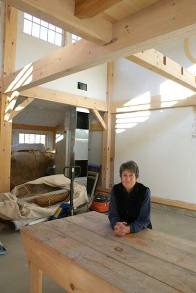 An artist sits at a table in her recently renovated studio, with white walls and wooden beams