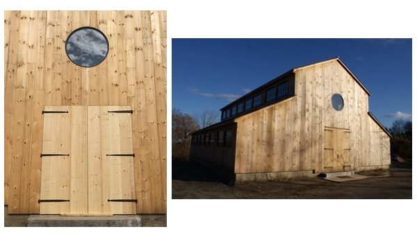 The exterior of a newly built, entirely wooden barn