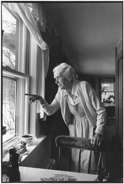 Black and white picture of an elderly woman pointing out a window