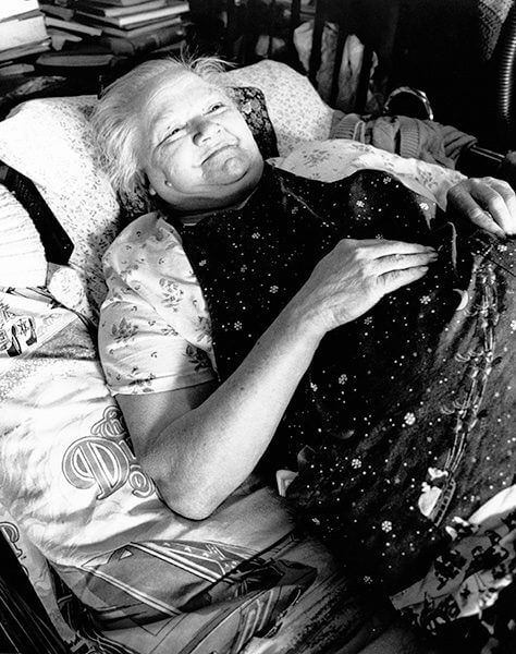 Black and white photo of a woman laying on her back in bed