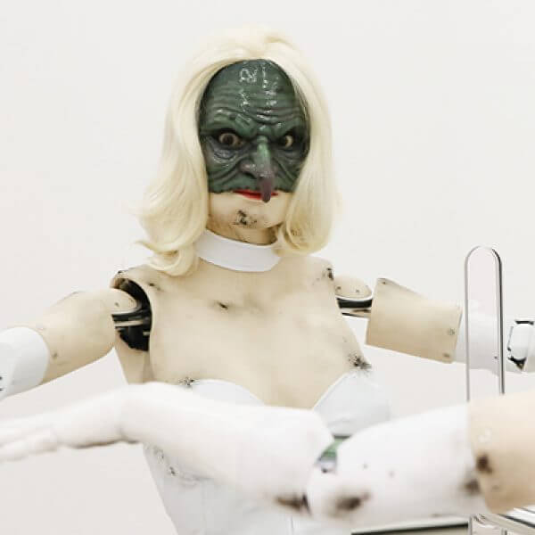 A sculpture of a humanoid robot wearing a blonde wig and grotesque half mask