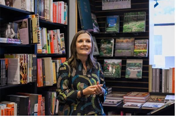 A writer gives a talk at a bookstore in front of shelves