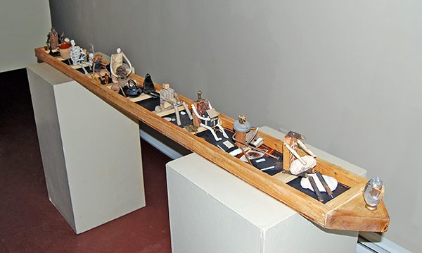 Found object sculpture of a group of wooden figures in a boat