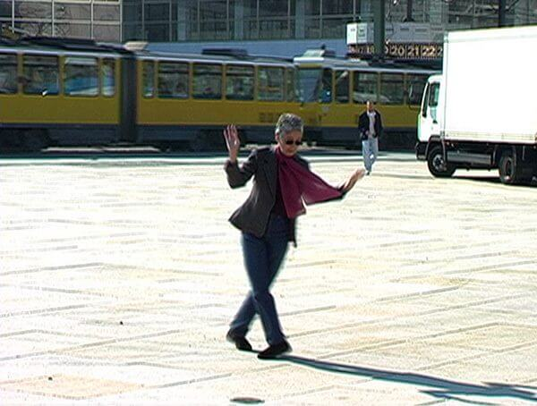 A shot from a video of a woman in a purple scarf dancing on an empty street square