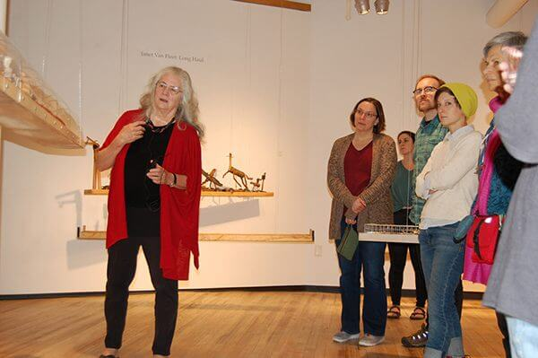 An artist at a gallery speaks to a crowd looking at her sculptures
