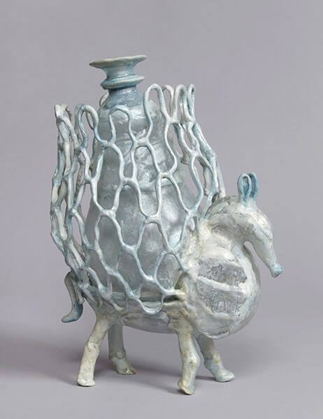 Sculpture of a horse-like animal with a netted vase on top