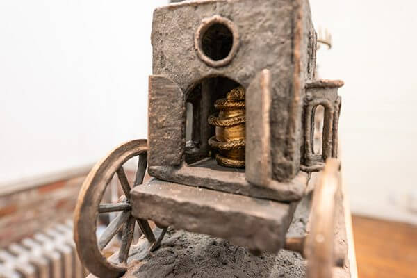 A bronze wagon carrying an egg with a snake wrapped around it