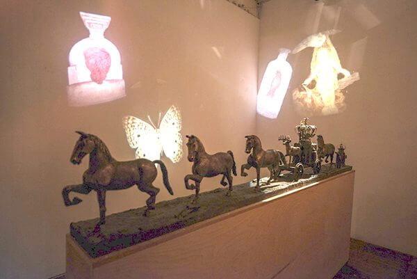 a bronze processional sculpture of horses and a wagon