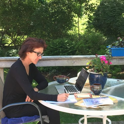 A woman working on a laptop and notepad on an outdoor deck
