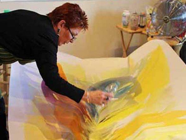 Bette Ridgeway pouring paint in her studio