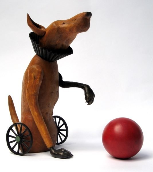 Wooden sculpture of a dog with his ball