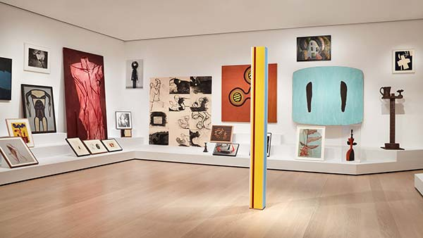 Installation view of sculptures, drawings, and paintings on the wall and lining shelves of a gallery
