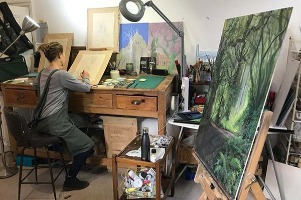 Artist drawing trees at a workman's desk