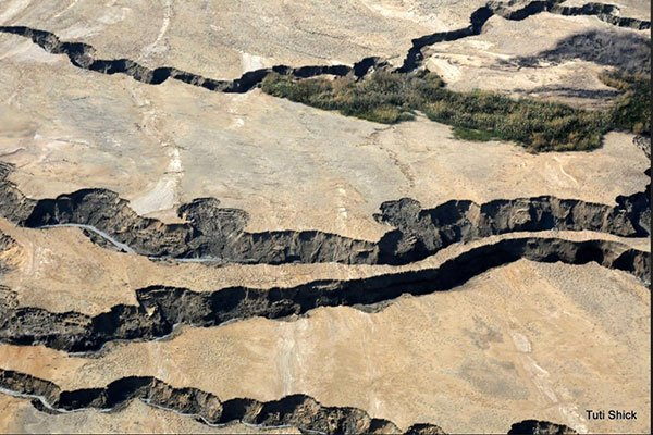 An aerial photograph of dry earth with fissures