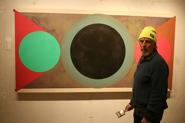 Painter Sandy Sokoloff in front of one of his works