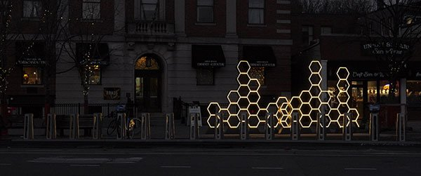 An installation of lit honeycomb-like shapes on a city sidewalk