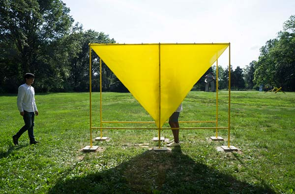 A bright yellow latex sheet, an interactive sculpture installed in a park