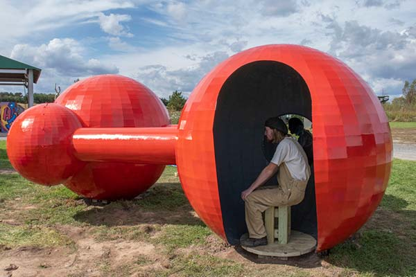A red spherical sculpture in a park with people sitting inside one of the spheres