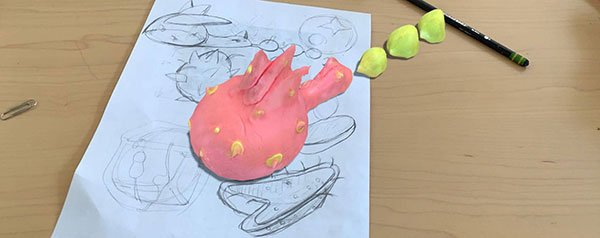 An AR visualation of a pink and yellow creature on a desktop