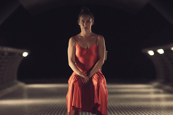 In a still from a short film, a dancer in a red dress sits on a chair.