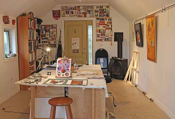A worktable lined with paintings and the entrance to an artist's studio
