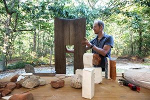 Mark Webber works on a wood sculpture outside his studio