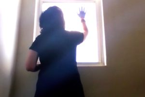 A woman wearing gloves looks out a bright window